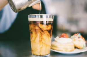 Creamy iced coffee being poured into a clear glass